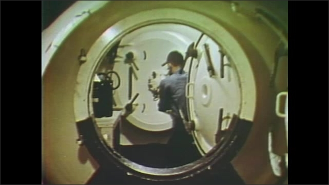1960s: UNITED STATES: space and submarine medicine research. Submarine carbon dioxide capsule. Astronauts perform cognitive tasks during experiment inside chamber