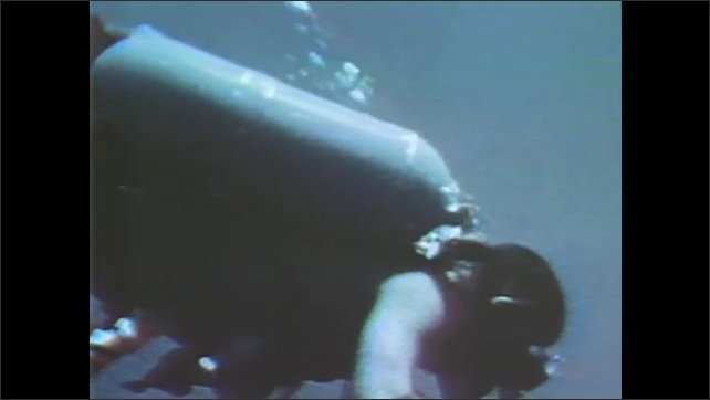1960s: UNITED STATES: astronauts scuba diving. Men swim underwater. Air bubbles during scuba dive