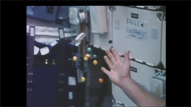 1990s: Hand releases peanut M&Ms in zero gravity. Candy floats from open hand on cabin of space shuttle.