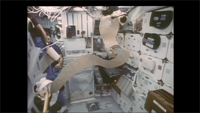 1990s: Astronaut with long roll of printer paper floats past colleague in zero gravity.