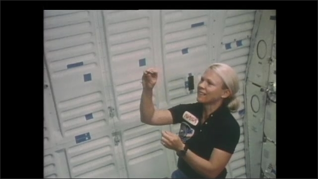 1990s: Astronaut release jacks and ball into zero gravity. Woman plays jacks in zero gravity.