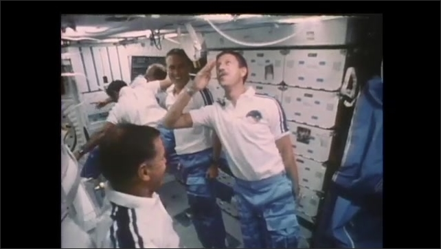 1990s: Astronauts mimic military movements and marching in zero gravity. Astronauts salute and smile.