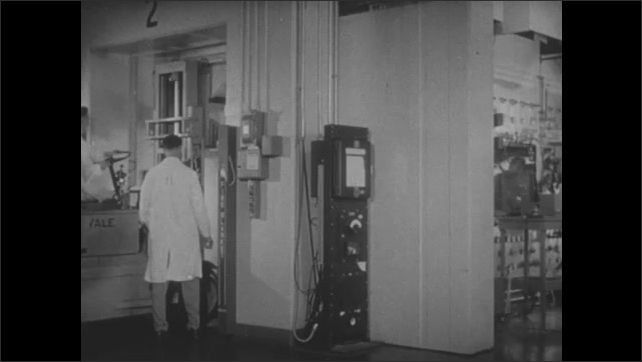 1950s: Small forklift drives into laboratory. Man uses joystick to move mechanical hand.