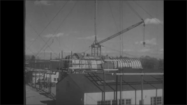 1950s: Completed steel sphere testing environment. Crane over full-scale model of nuclear engine.