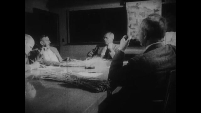 1950s: UNITED STATES: insects on damaged crops. Men meet around table. Men in meeting