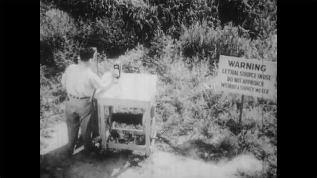 1950s: UNITED STATES: crops in field. Warning sign in lab grown crop field. Scientist operates windlass in field