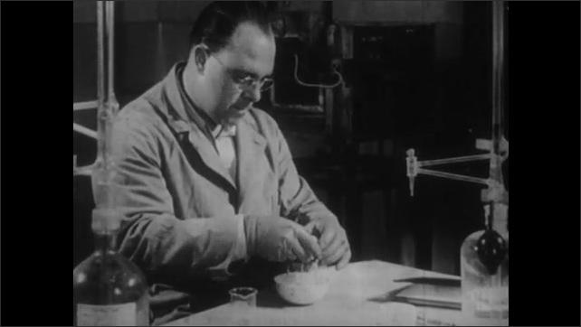 1950s: UNITED STATES: man holds egg in lab. Man cracks egg in bowl. Man splits egg white from yolk.