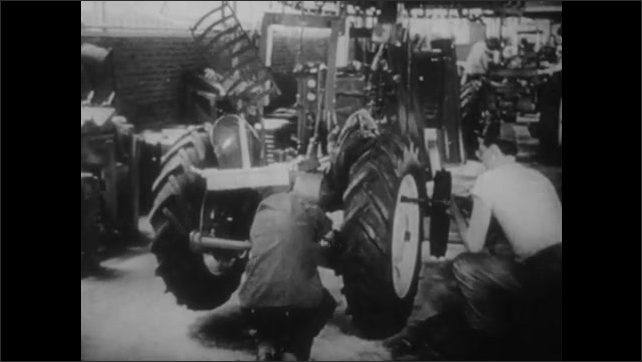 1950s: UNITED STATES: Man climbs down from tractor. Man walks around tractor. Tractor inside factory. Piston Rings in factory