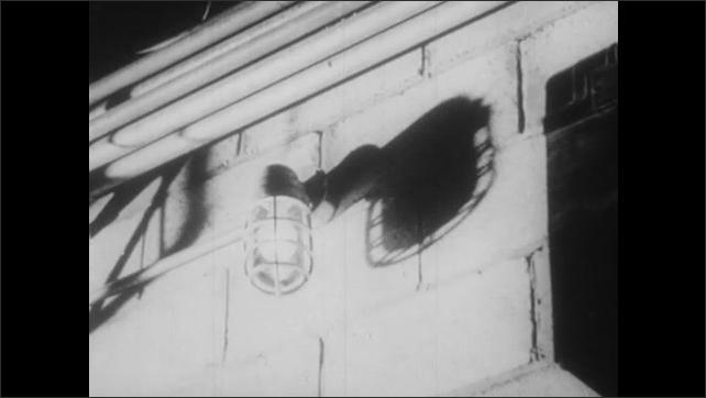 1950s: UNITED STATES: operator controls reactor pile. Man monitors reactor