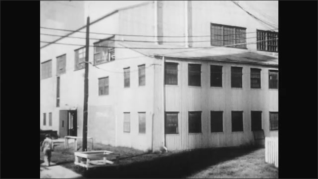 1950s: UNITED STATES: chain reaction as atoms explode. Workers at building. Men get into car
