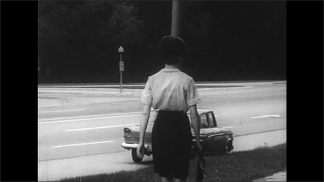 UNITED STATES 1960s: close up of woman walking on the street / woman walking in the street