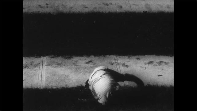 UNITED STATES 1960s: woman hitting man with handbag / man lying on floor