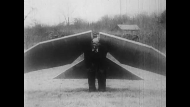 1930s: Man strapped into flying costume with two wings and a tail describes his invention.