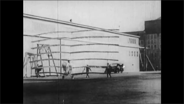 1930s: Helicopter style airship with multiple rotors raises a few feet off of the ground. Airplane with levels of wings taxis and collapses. Man in simple airplane as another man spins the propeller.