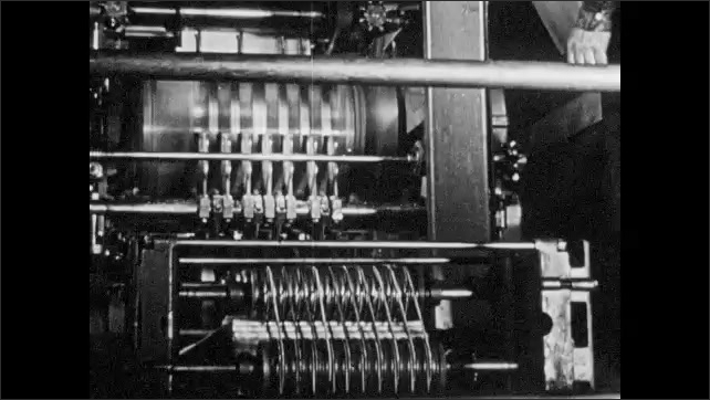 1940s: Woman throws lever on large factory loom. Printing presses print newspapers.