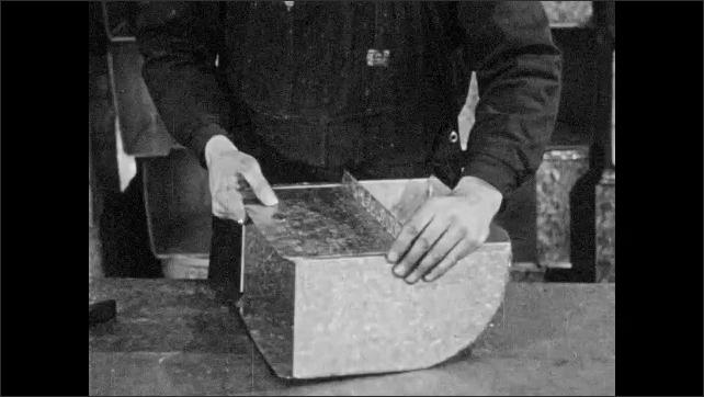 1940s: Man hammers sheet metal in factory, constructing vent shaft. Man builds vent shaft. Man cuts sheet metal. Man shapes sheet metal into shaft.