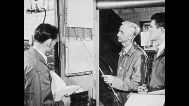 1940s: Teacher in front of engineering class holds up light bulb suspended by magnetic electricity. Man points at back of HVAC system. Two men constructing small hut.