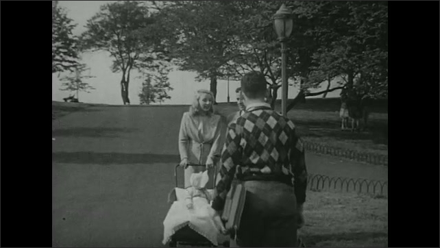 UNITED STATES 1940s: Couple with baby in park, boy stops and looks at baby.
