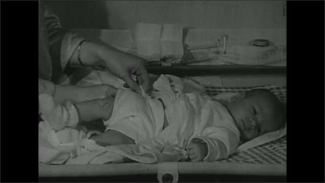 UNITED STATES 1940s: Baby having diaper changed.