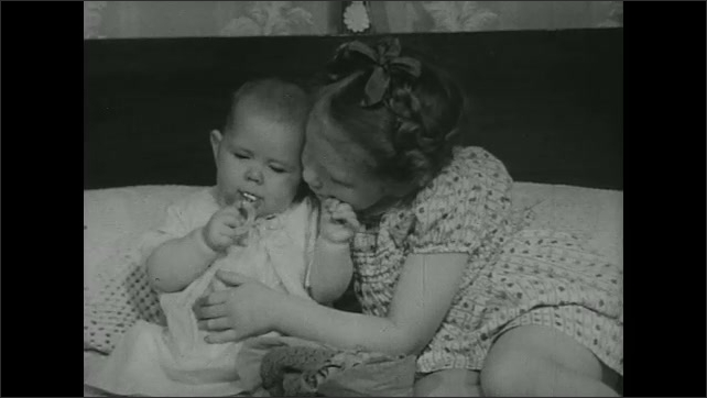 UNITED STATES 1940s: Girl sits on bed with baby.