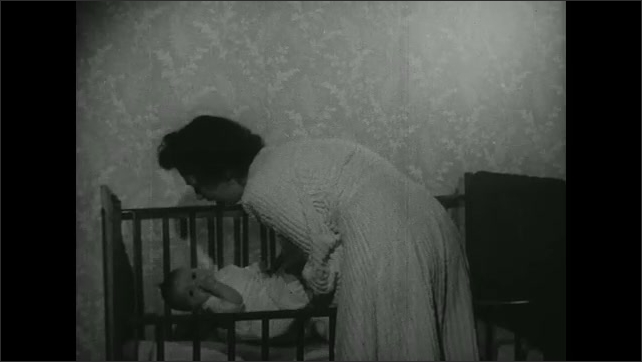 UNITED STATES 1940s: Mother puts baby on lap / Mother puts baby in crib.