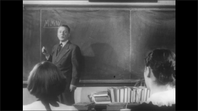 1950s: Man at front of classroom speaks and sets glasses on table. Man writes on chalk board. Man speaks to class. Man draws lines on chalk board. Man speaks to class.
