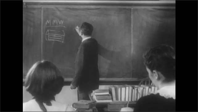 1950s: Man speaks and stands near chalk board. Students sit in classroom. Boy raises had and speaks. Man responds and draws trees on board. Students sit in classroom.