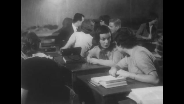 1950s: Students sit at desks in class and listen. Girls speak. Students lean on desks and talk. Man writes on chalk board.