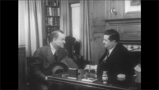 1950s: Men sit in office. Man gestures with hat and speaks to man behind desk. Man behind desk nods and responds.