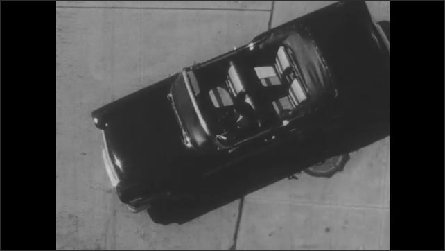 1950s: UNITED STATES: overhead view of car driving. Driver checks for traffic. Car leaves curb and turns onto street. Man speaks to camera. Skills on Hills title