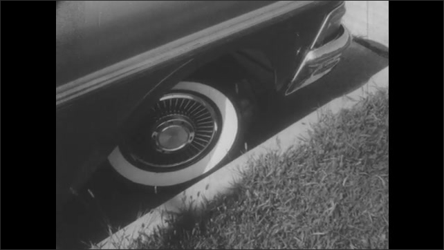 1950s: UNITED STATES: close up of front tire by curb. Man drives car. Man in open top car