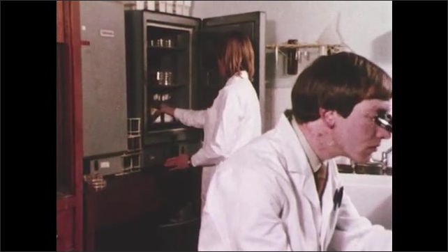1970s: woman in lab coat opens refrigerator, places bottles on shelf and closes door as man sits at desk and adjusts microscope in laboratory. single cell organism glows while DNA chain lights up.