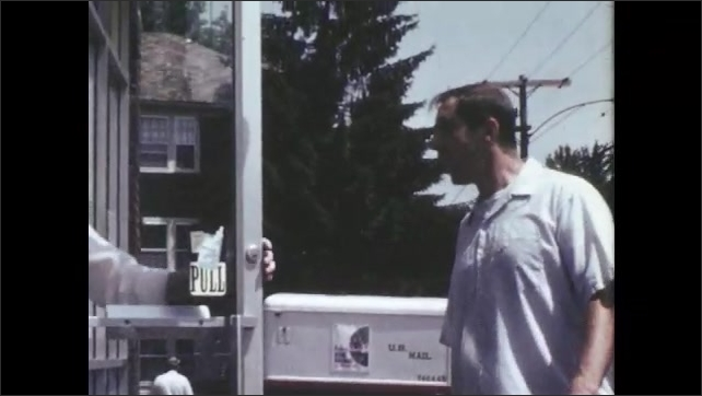 1960s: UNITED STATES: man walks towards gates. Man carries bag. Man walks to work. Man puts melons in trolley