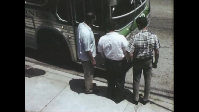 1960s: UNITED STATES: men stand on curb. Men wait for bus. Men get into bus.