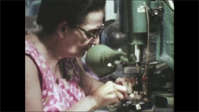 1960s: UNITED STATES: lady loads thread through sewing machine. Lady ties knots with thread