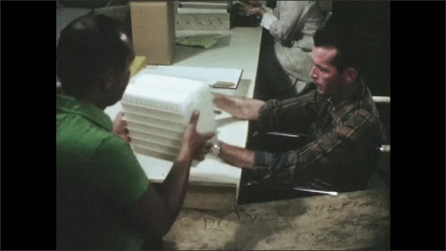 1960s: UNITED STATES: man teaches lady skills. Ladies work in workshop. Ladies work at bench together.