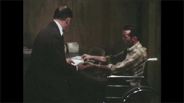 1960s: UNITED STATES: Men have meeting in office, Man in wheelchair talks to man at desk. Man looks at drawing. Man solves problem