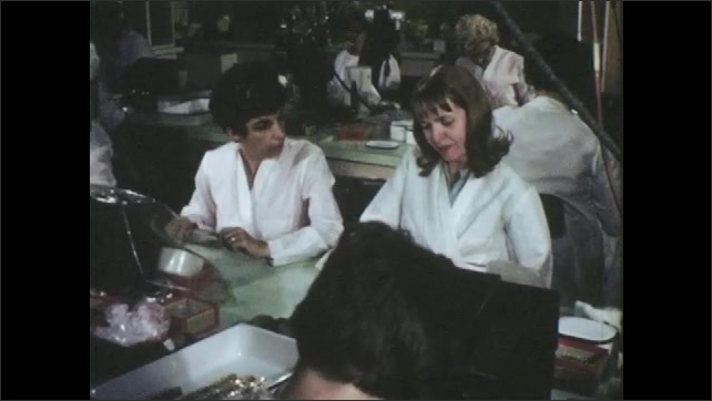1960s: UNITED STATES: ladies work at bench. Lady cries at bench.
