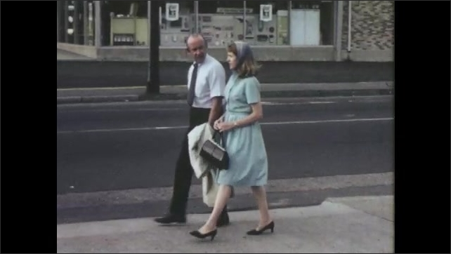 1960s: UNITED STATES: lady and man walk in street. Man talks to lady on street. Couple walk to car