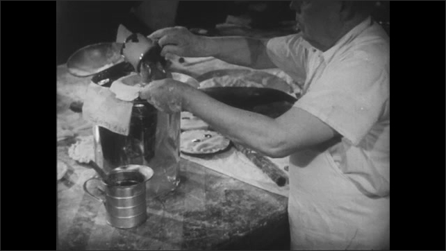 Preparing a pie, a baker places a cupful of fruit inside a pie crust.