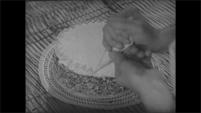 Bakers at work as frosting is placed on cake.