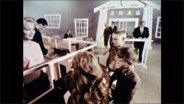 1960s: Kids walk through revolving door into pretend bank. Couple walks down pretend street, walks into bank, sits down at desk with bank employee. Kids deposit money with bank teller.