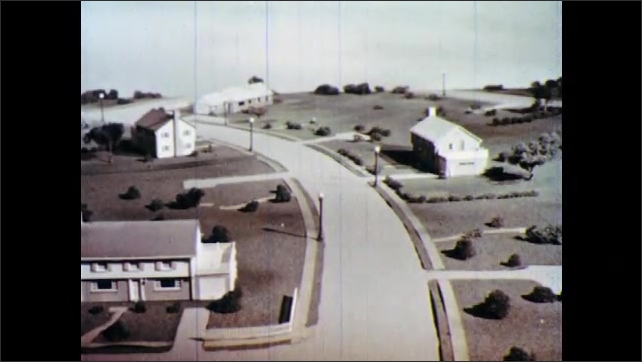 1960s: Model of town. Houses, buildings, trees, and cars pop up on model.