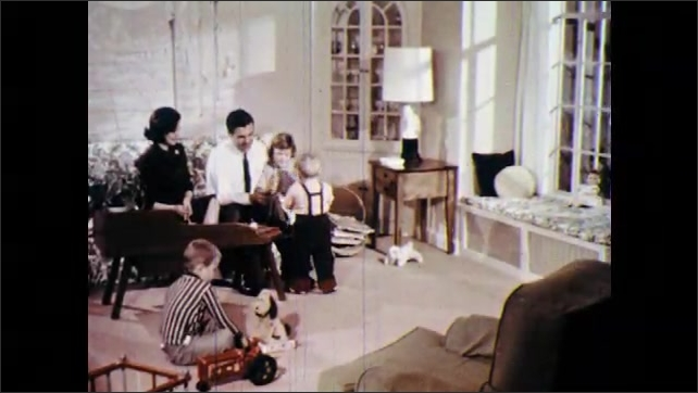 1960s: Couple sits in living room, reads magazine together. Child sits on chair, plays with doll, boy sits on floor, plays with toy. Baby sits on floor, looks around. Family plays in living room.