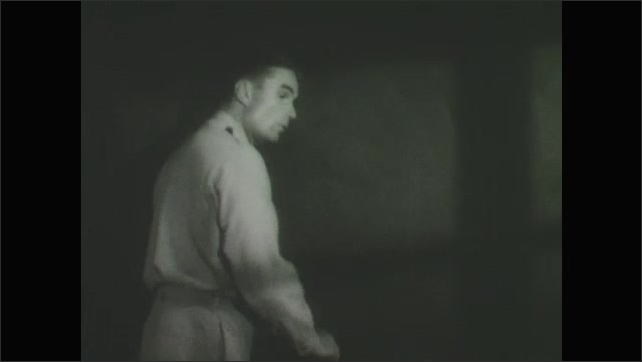 1950s: Soldier speaks and erases chalkboard.  Man pulls down diagram.