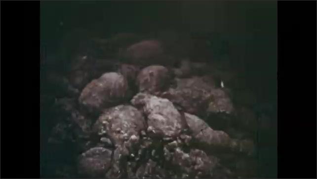 1970s: Light shines on ocean floor of Cayman Trough. Robert Ballard pilots bathyscaphe, shining light on ocean floor. Lava formations.