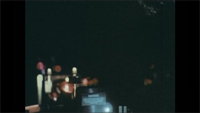 1970s: Lasers beam in a darkened lab.
