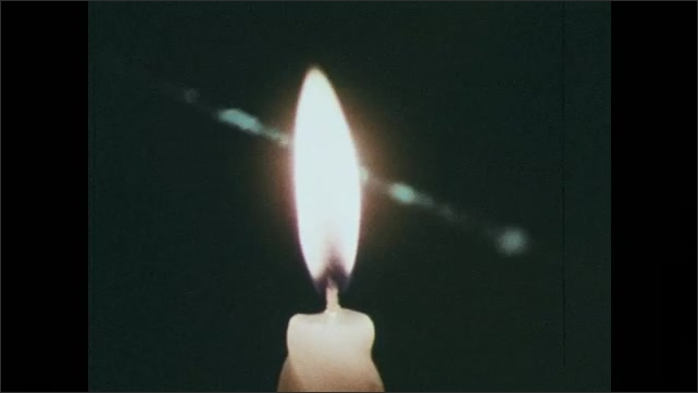 1970s: Laser beam sparks against stone. Close-up of an eye as laser shines on it. Laser shines through a candle flame. Fingers type on computer keyboard as graph changes.