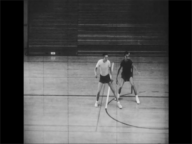 1960s: Teams of boys play basketball. Boys perform five man offense. Opposing team player guards boy closely in center court.