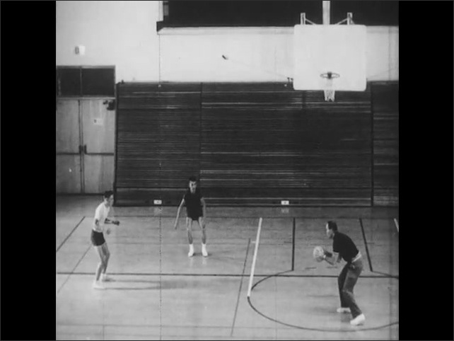 1960s: Coach fakes pass to boy being closely guarded. Boy retreats to basket. Opposing team member guards boy closely. Coach shoots basket.